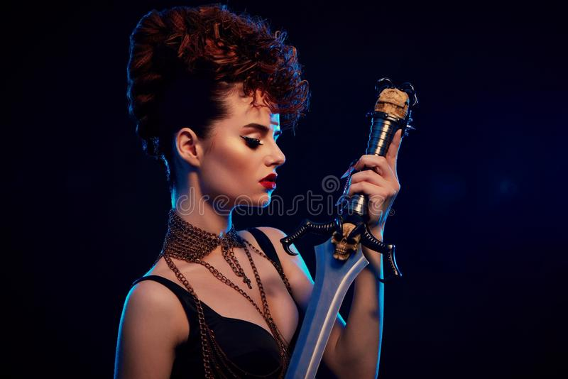 Stylish woman with fashionable hairdress holding steel sword. Portrait of young model with make up holding steel sword with black skull. Warrior wearing stylish stock photos
