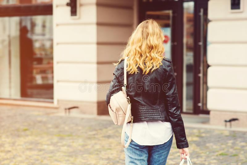 Stylish woman going to shopping. Consumerism, shopping, sales, lifestyle concept. Back view of happy woman with backpack. Urban royalty free stock images