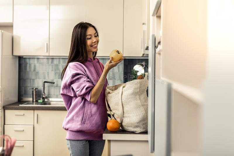 Stylish woman with long dark hair feeling excited before making salad royalty free stock image
