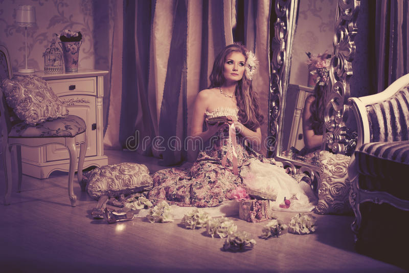 Stylish woman in a luxurious interior. Stylish woman in a vintage dress in a luxurious interior royalty free stock images