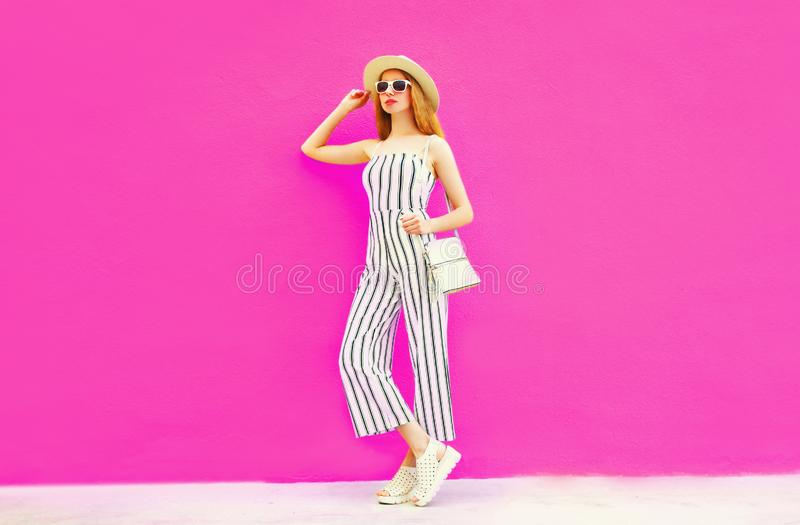 Stylish woman model in summer round straw hat, white striped jumpsuit posing on colorful pink wall. Background stock images