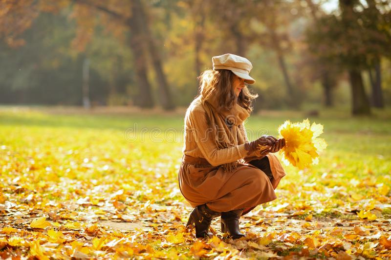Stylish woman outdoors in autumn park gathering leaves royalty free stock photos