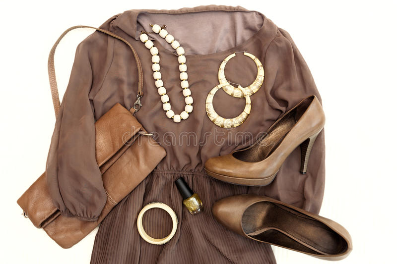 Stylish woman outfit. Brawn dress, shoes, purse, high heels shoes and beige accessories. Top view stock photos