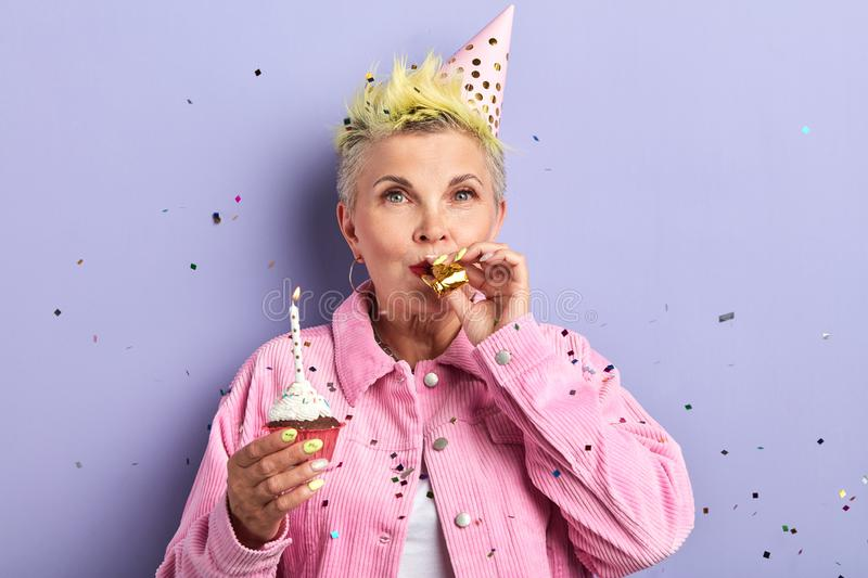 Stylish woman in party hat blowing noisemaker, celebrating birthday royalty free stock image