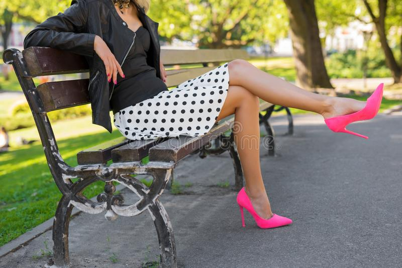 Stylish woman with pink shoes sitting on bench in park royalty free stock image