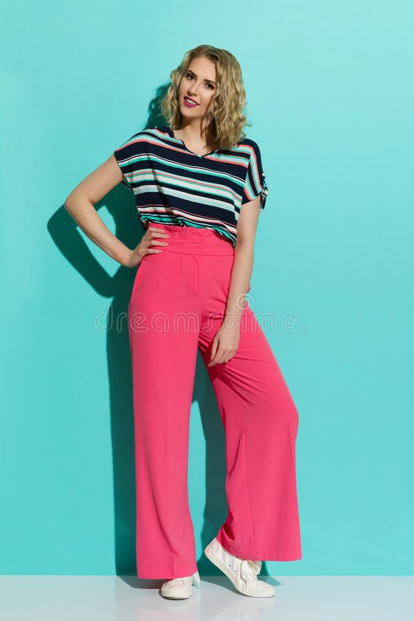 Stylish Woman In Pink Wide Legs Trousers, Sneakers And Striped Blouse royalty free stock photos
