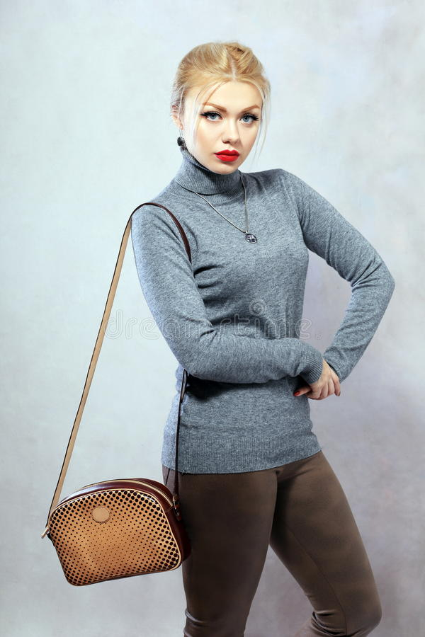 Stylish woman. Portrait of young blond woman posing in photostudio on neutral background royalty free stock photo