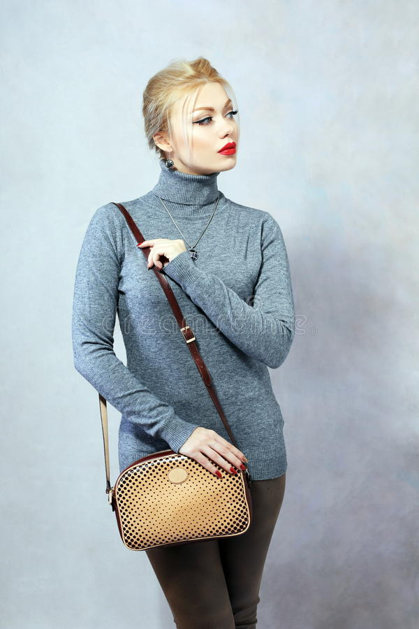 Stylish woman. Portrait of young blond woman posing in photostudio on neutral background royalty free stock images