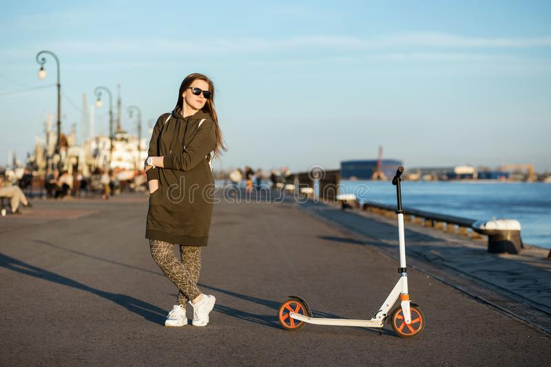 Stylish woman posing with kick scooter near blue river. She wearing in green hoody, white sneackers. sunglasses. Active royalty free stock images