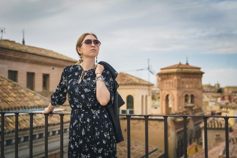 Stylish woman posing in the old part of the town against tile roofs. Medieval city of Toledo in the center of Spain. royalty free stock images