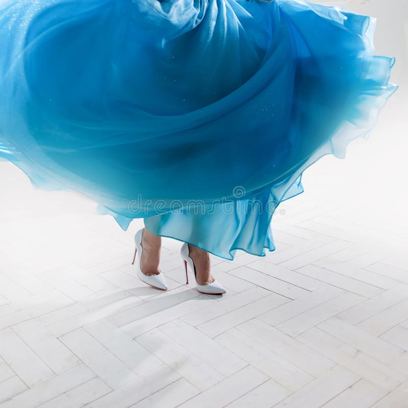 Stylish woman`s feet in a puffy skirt and white shoes. royalty free stock photography