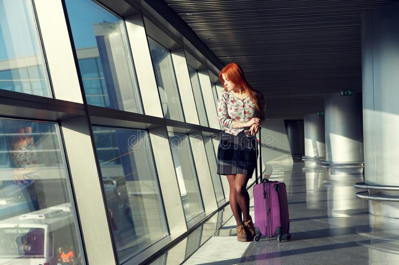 Stylish woman with a suitcase standing at the window at airport. traveler waiting airplane flight. Stylish woman with a suitcase standing at the window at the stock photos