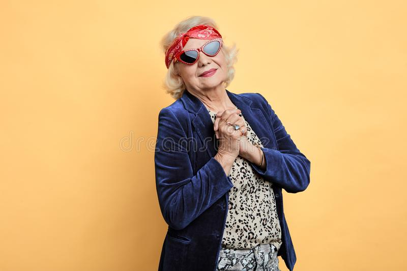 Stylish woman in sunglasses blue jacket, dress keeping her palms crossed royalty free stock photos
