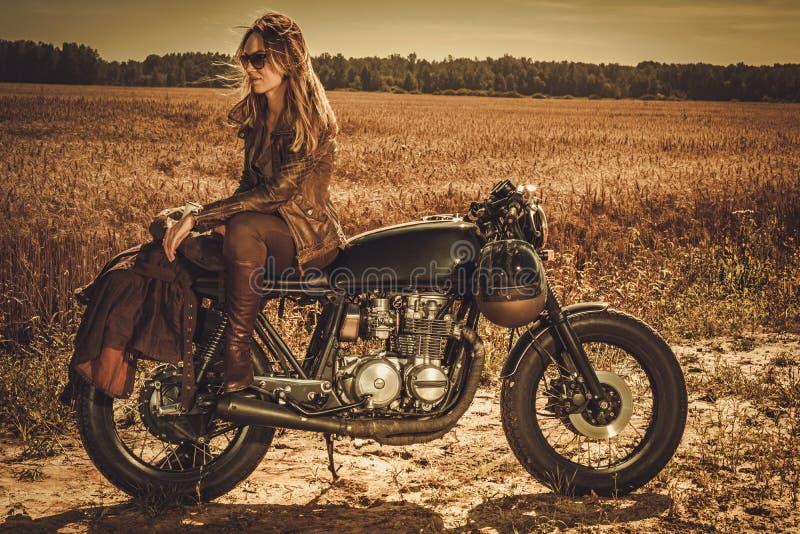Stylish woman on the vintage custom cafe racer in a field. Young, stylish woman on the vintage custom cafe racer in a field stock photo