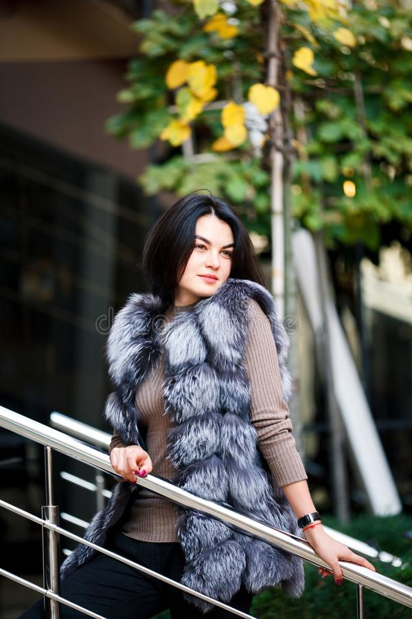 Stylish woman walking In the city in Fur-Vest. Urban street style, fashion trend. Fashion outdoor photo of beautiful woman stock images