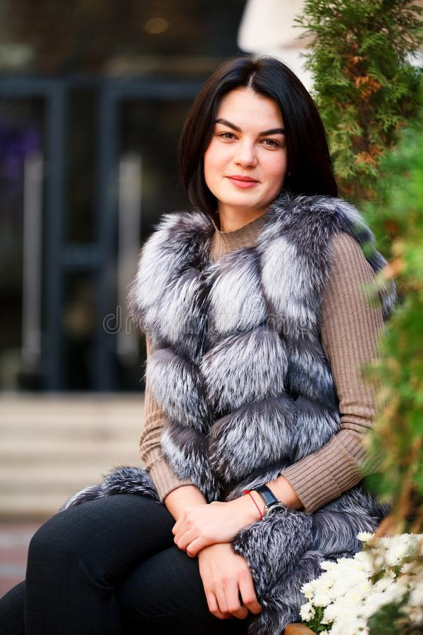 Stylish woman walking In the city in Fur-Vest. Urban street style, fashion trend. Fashion outdoor photo of beautiful woman royalty free stock images