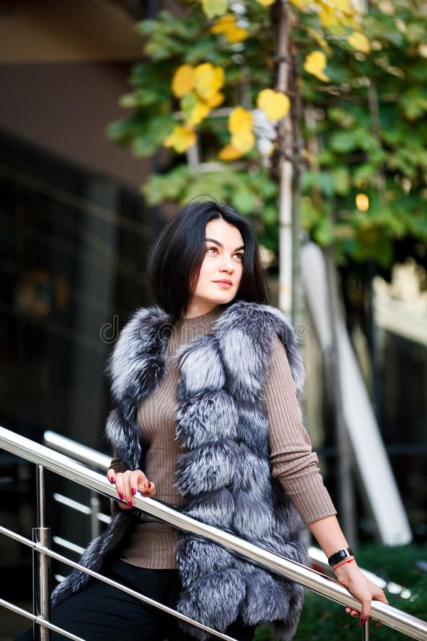 Stylish woman walking In the city in Fur-Vest. Urban street style, fashion trend. Fashion outdoor photo of beautiful woman stock image