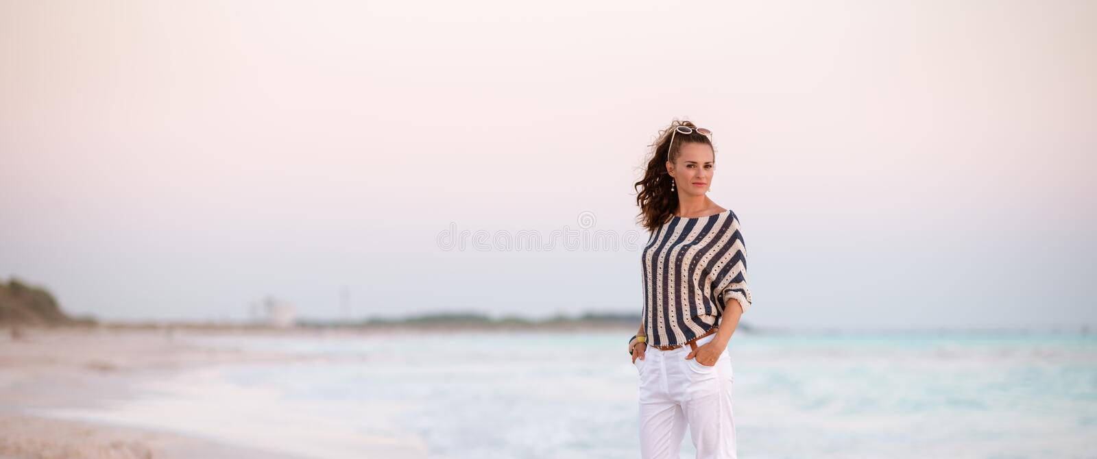 Stylish woman on beach in evening royalty free stock photography