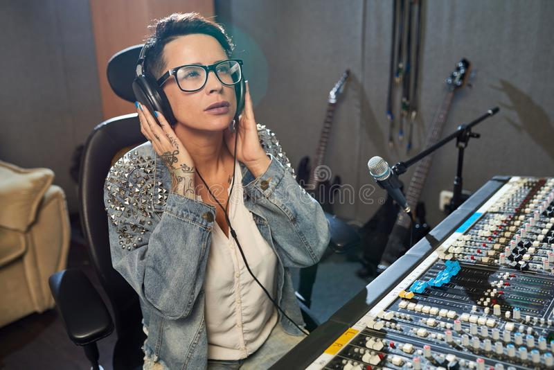 Stylish woman working in sound studio stock images