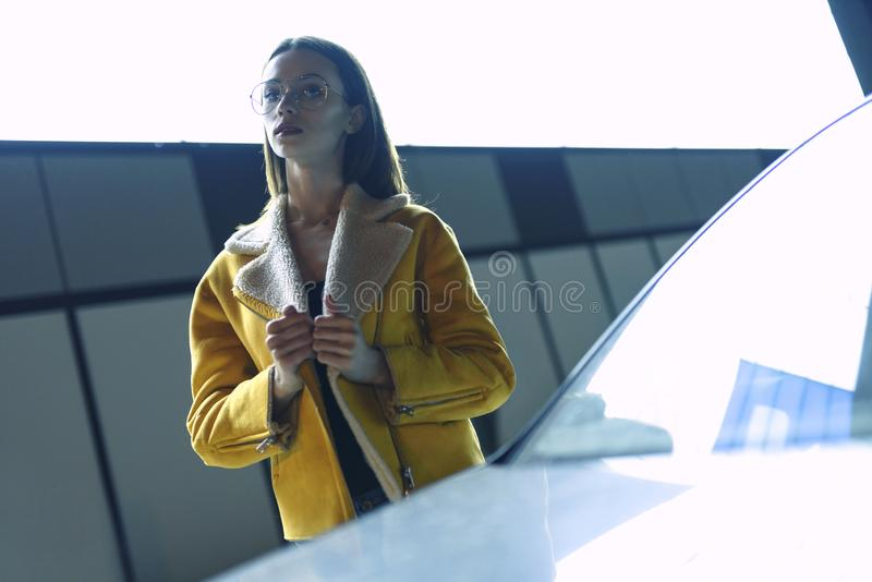 Stylish woman in yellow jacket and glasses. Posing on city center, lit by bright light. Womenswear fashion stock image