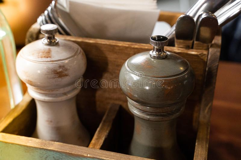 Stylish wooden salt and pepper mills in a wooden crate on a restaurant table royalty free stock photo