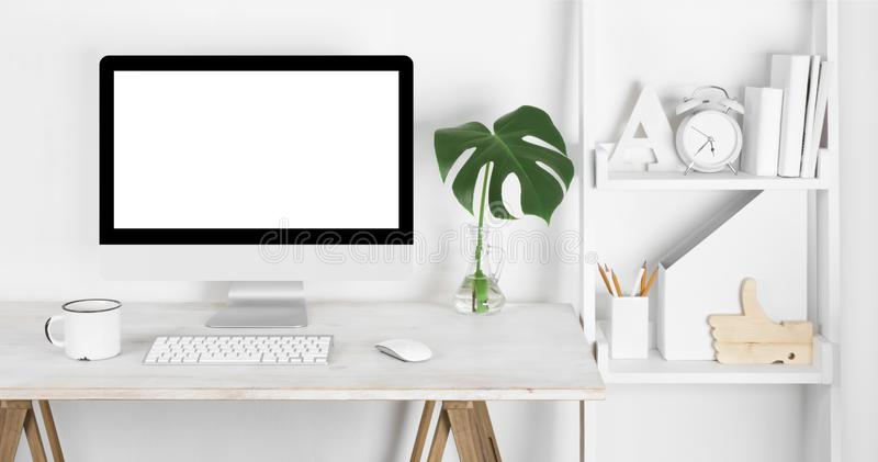 Stylish workplace concept with vintage wooden table, computer and shelves royalty free stock images