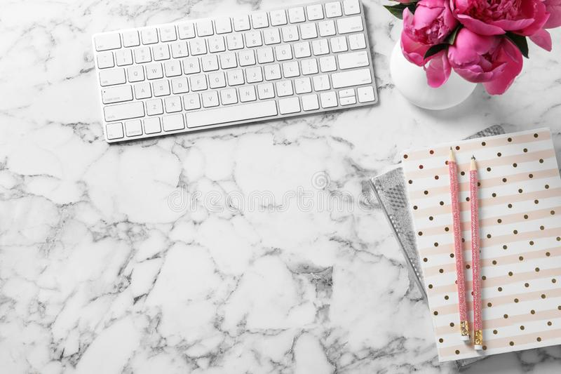 Stylish workplace with fragrant peonies on marble table, flat lay stock photo