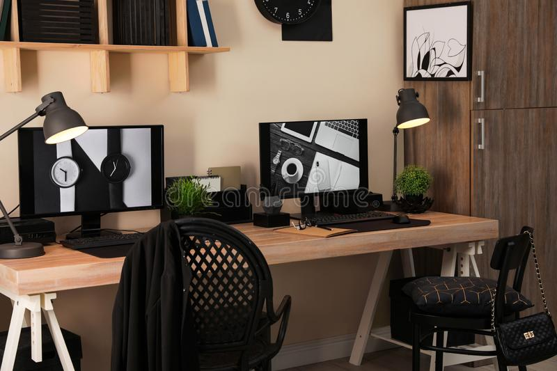 Stylish workplace interior with computers. On table royalty free stock images