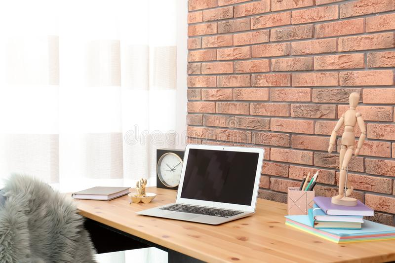 Stylish workplace interior with laptop on table near brick wall stock image