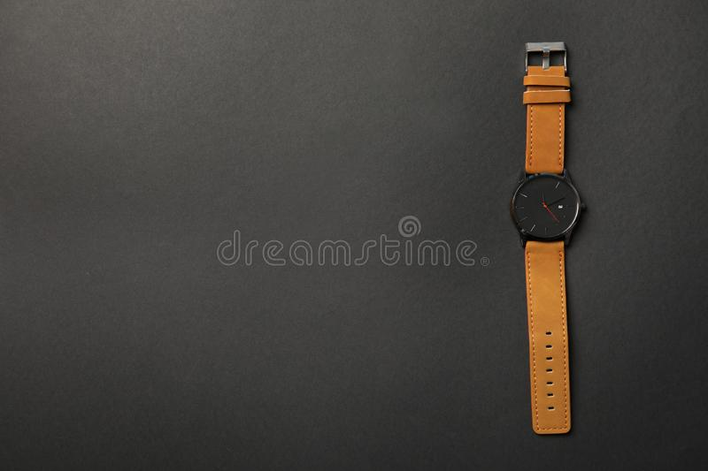 Stylish wrist watch on dark background, top view with space for text. Fashion accessory royalty free stock photos