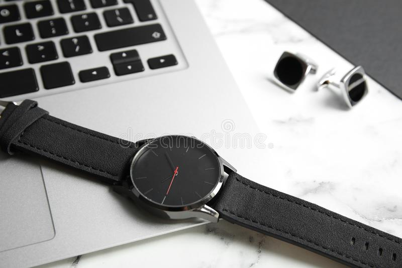 Stylish wrist watch and laptop on marble table. Time management stock photos