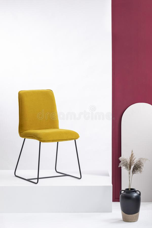 Stylish yellow chair on white platform in elegant showroom with white and purple walls. Real photo stock image