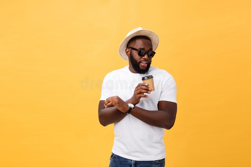 Stylish young african american man holding cup of take away coffee isolated over yellow background. Stylish young african american man holding cup of take away stock image