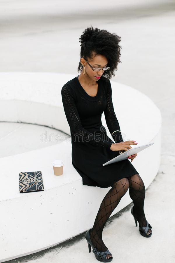 Stylish young afro hair professional woman using tablet stock image