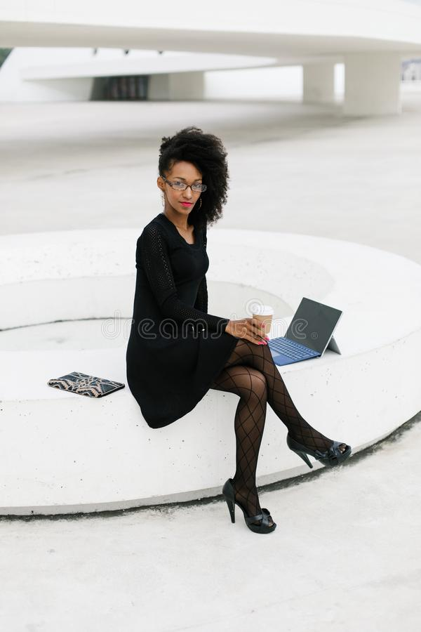 Stylish young afro hair professional woman using tablet stock images