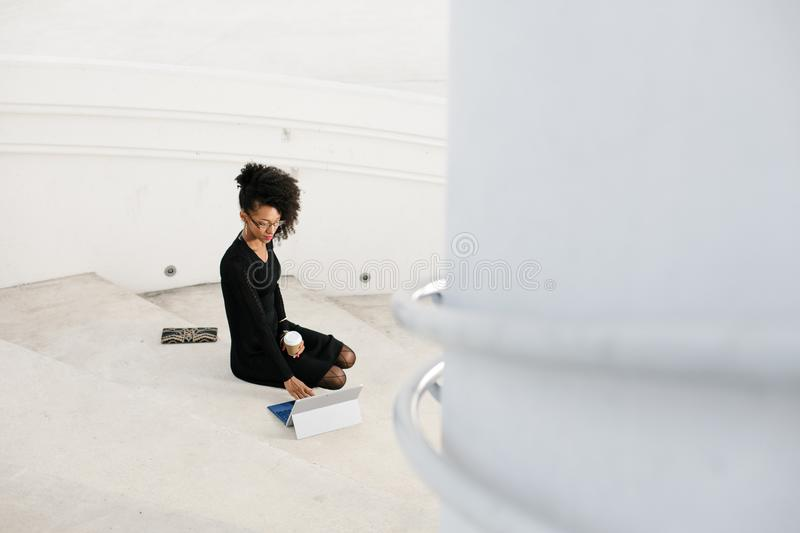 Stylish young afro hair professional woman using tablet stock photo