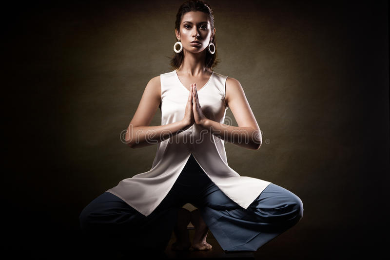 Stylish young athletic girl in fashionable clothes, showing yoga asanas in the studio. Beauty face and body health. Stylish young athletic girl in fashionable stock photography