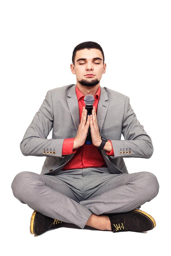 Stylish young bearded guy in a gray suit and with a microphone is meditating while sitting in the lotus position royalty free stock image