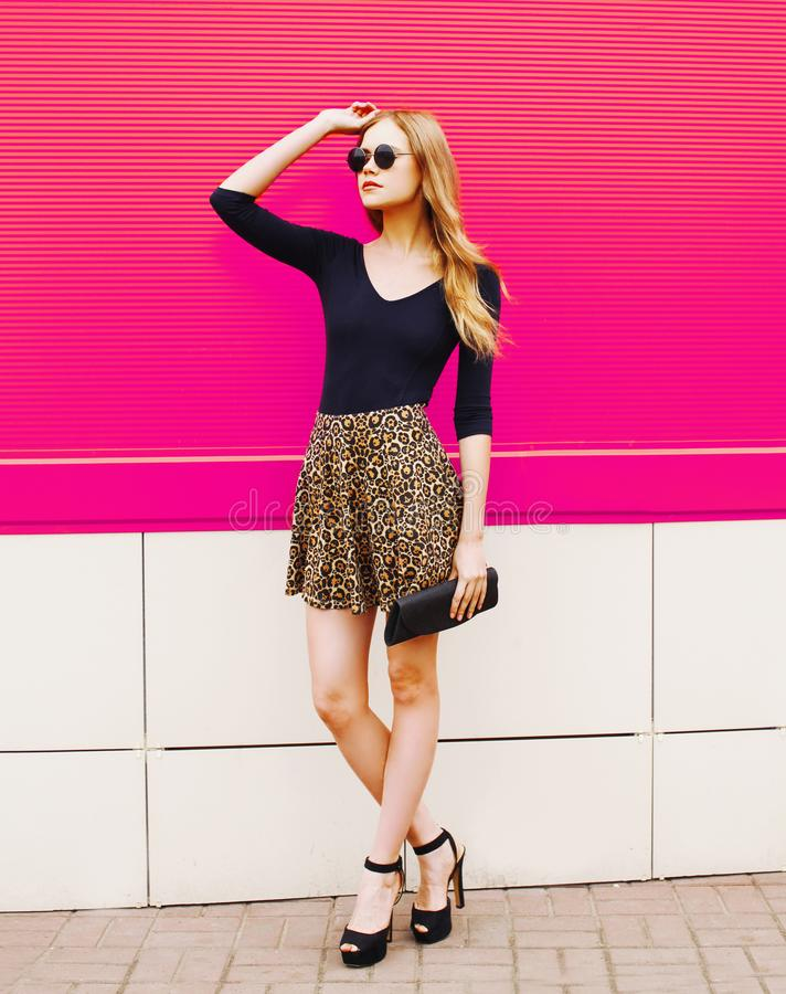 Stylish young blonde woman in leopard skirt, sunglasses with handbag clutch posing on city street royalty free stock photography