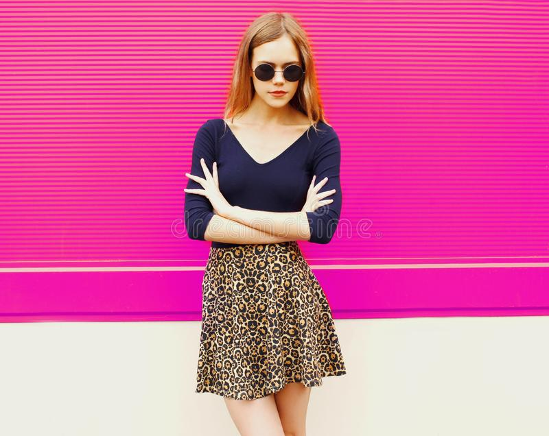 Stylish young blonde woman posing in leopard skirt and sunglasses on city street royalty free stock photos