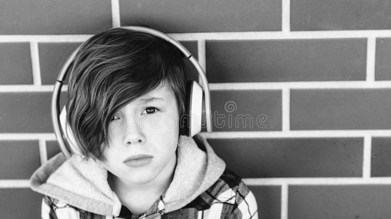 Stylish young boy in headphones listening to music over brick wall. Teenages and emotions concept. Sad handsome boy teen with stock image