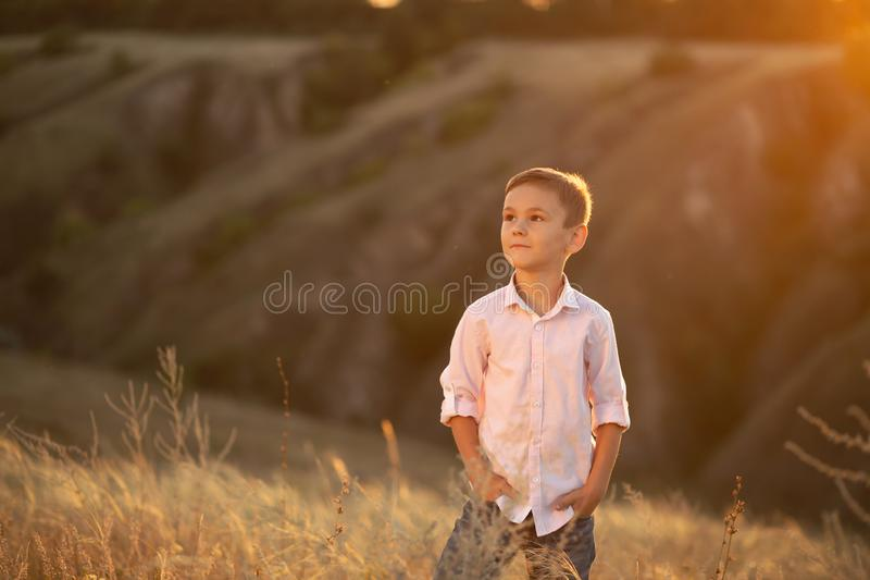 Stylish young boy posing in field at sunset stock images