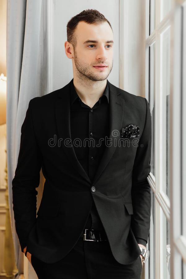Stylish young bristle man is standing near the big vintage window and looking far away. royalty free stock photo