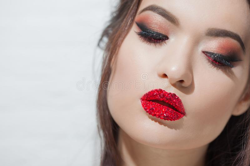 Stylish young brunette with bright and stylish makeup. Eye shadow with arrows and bright red lips royalty free stock images