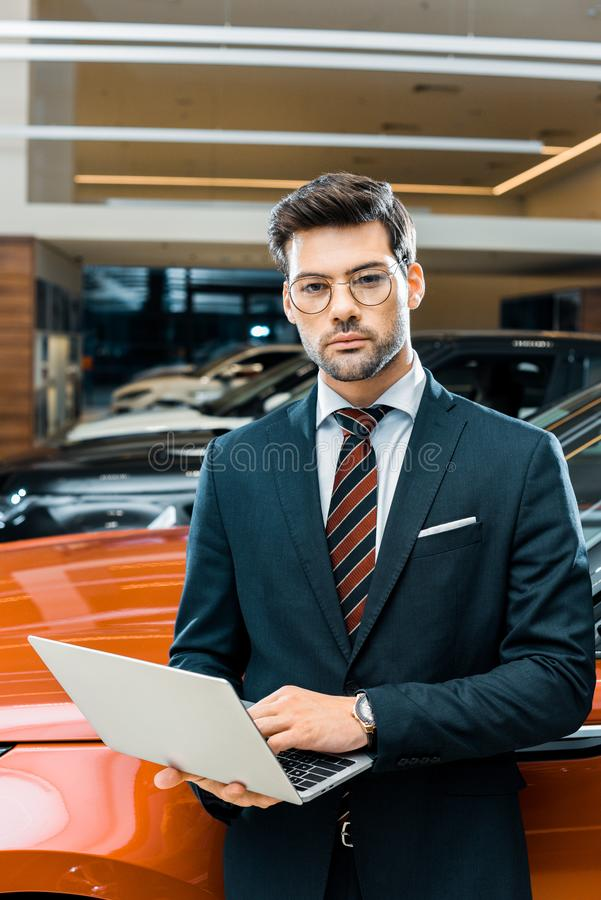 Stylish young businessman in eyeglasses. Using laptop near automobile royalty free stock photos