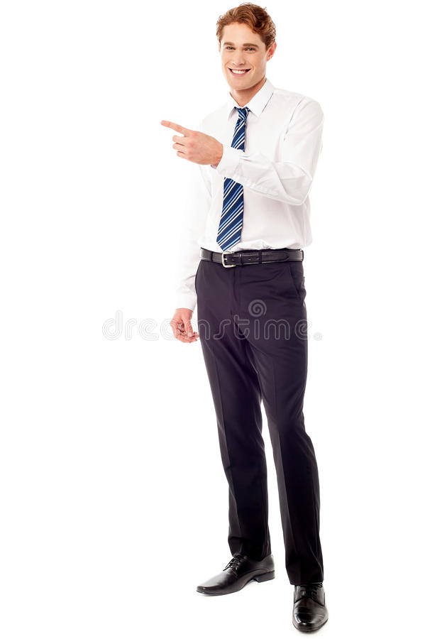 Stylish young businessman pointing away stock image