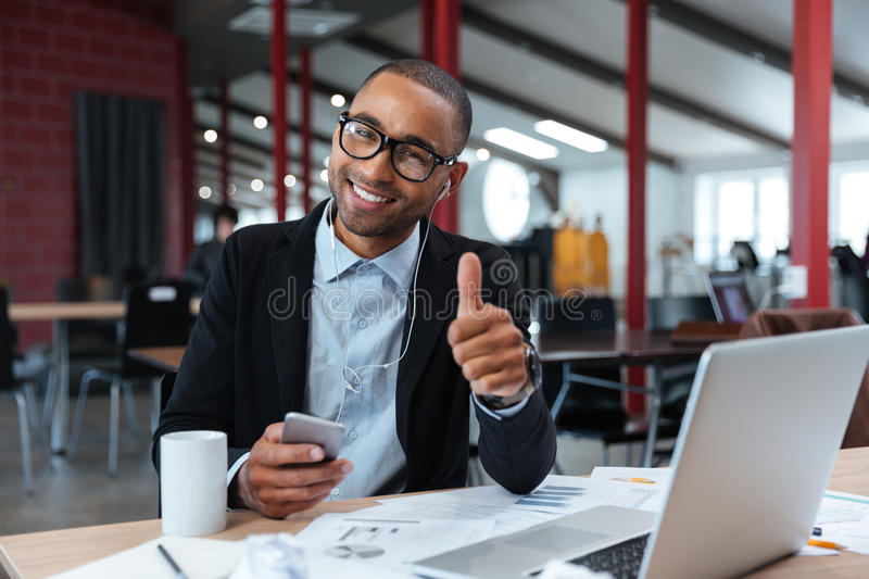 Stylish young businessman showing okay sign. And holding smartphone at the laptop royalty free stock photos