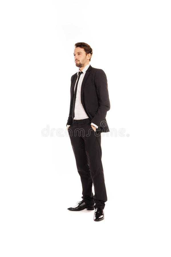 Stylish young businessman standing thinking. Staring into the distance with his suit jacket unbuttoned and hands in his pockets, full length view isolated on stock photography