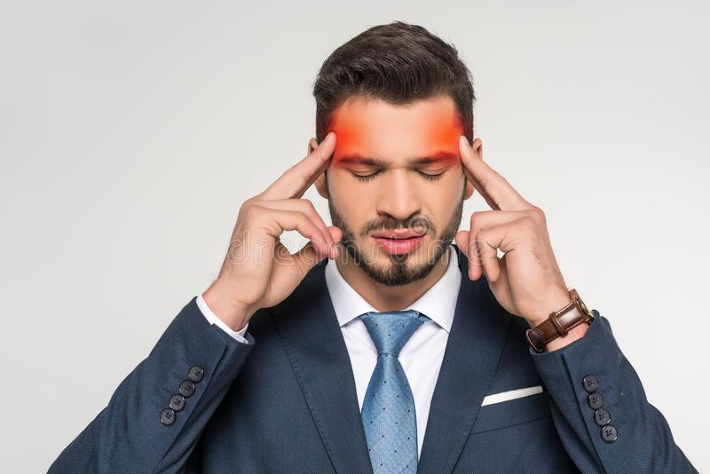 Stylish young businessman suffering from headache. Isolated on grey royalty free stock photography