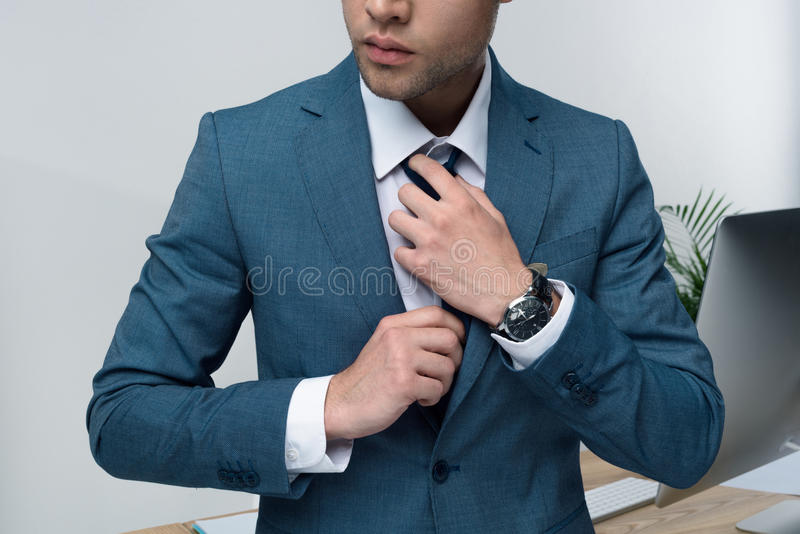 Stylish young businessman in suit adjusting tie in office. Cropped shot of stylish young businessman in suit adjusting tie in office stock photos